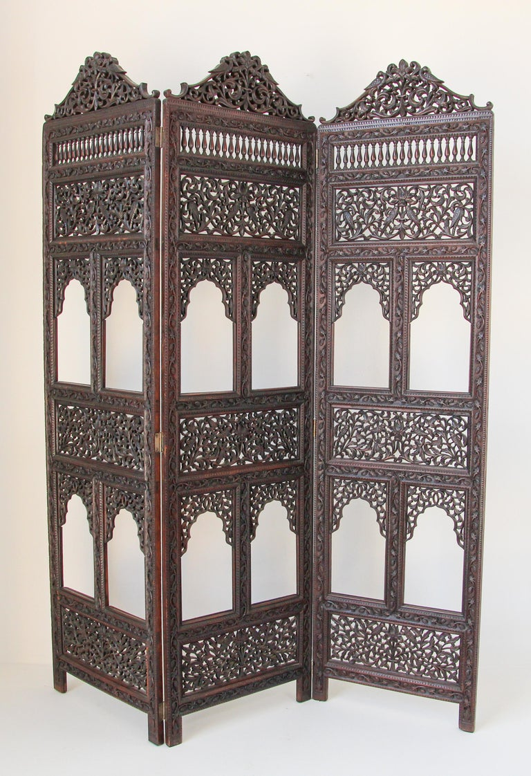 Anglo-Indian hardwood three-panel Screen. This is a beautifully carved sculptural rosewood Anglo-Indian Wooden screen in Victorian colonial Raj style featuring intricately carved floral-foliage fretwork, Fine quality late 19th century (circa 1880)