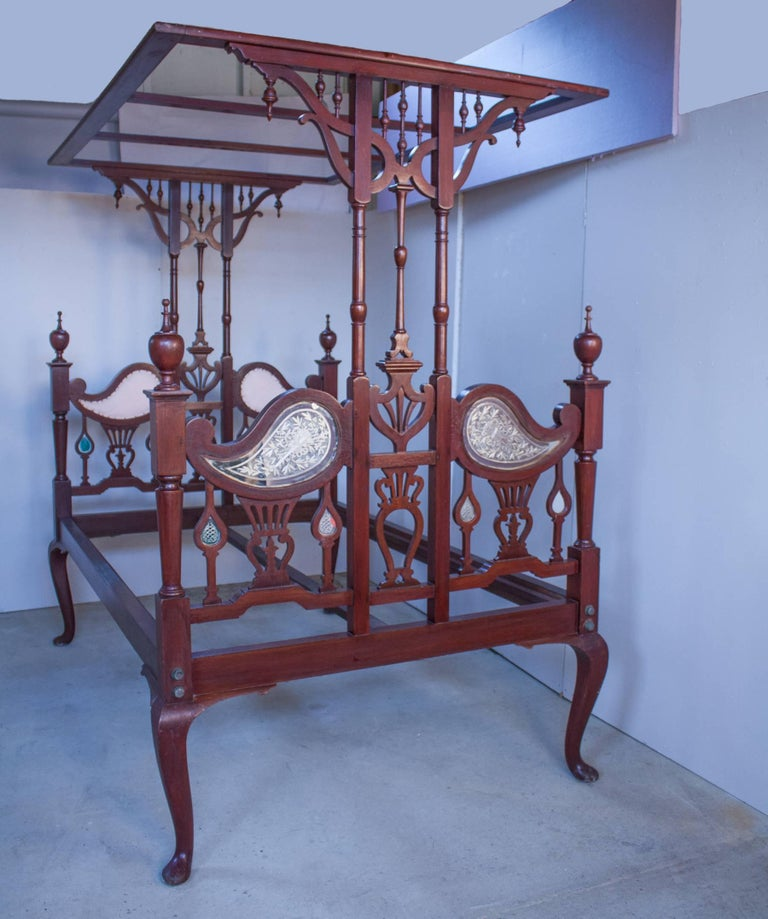 A richly toned mahogany bed with tester canopy from northern India, circa 1930. The intricately carved frame has mirrors reverse etched with musical instruments on the outside of the head- and footboards and upholstery on the inside. The frame comes