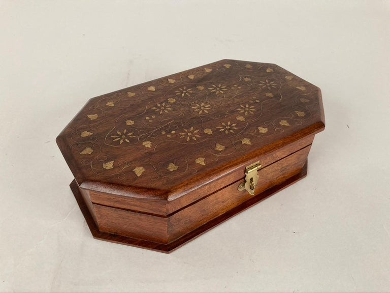 An octagonal form hand carved rosewood box with the top inlaid with brass in a floral design. Elegant eight sided form accents the grain of the rosewood.