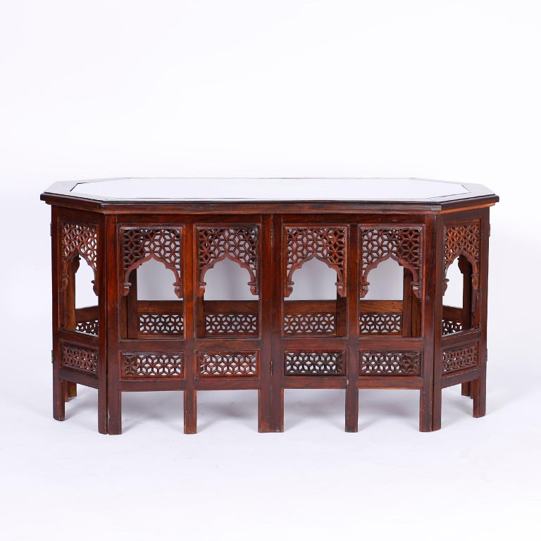 Antique Anglo Indian coffee table crafted in rosewood with a stylized octagon form featuring a carved open fretwork honeycomb top with an oval medallion inlaid with copper and brass and a brass inlaid border. The base has fourteen legs separated by