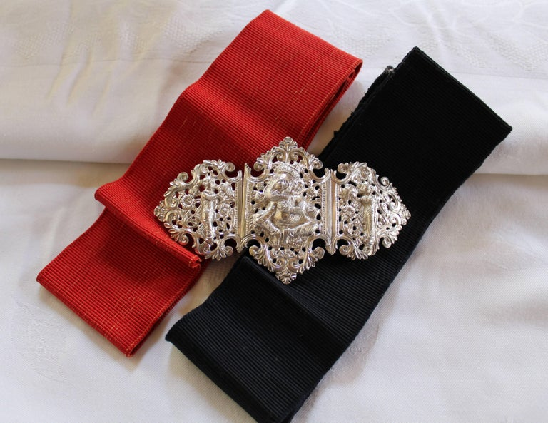 This is a highly ornate and decorative old Anglo-Indian silver belt buckle with red and black ribbon belts.  It dates to the early 20th century and is made up of three separate sections - two panels are joined by a hinge and the third separates to