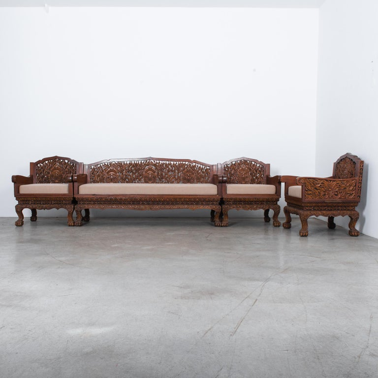 Intricately carved sofa set found in an orientalist style Belgian carriage house. From circa 1920s Southeast Asia, carved from dense rosewood and re-upholstered in warm cream fabric. This amazing set features stunning graphic relief of dragons face