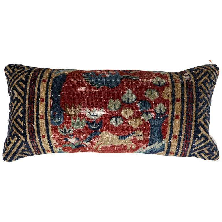 Bolster size pillow made from a mid-19th century animal motif Tibetan rug in red blue and camel. Backed in cotton, zipper closure provided too.
