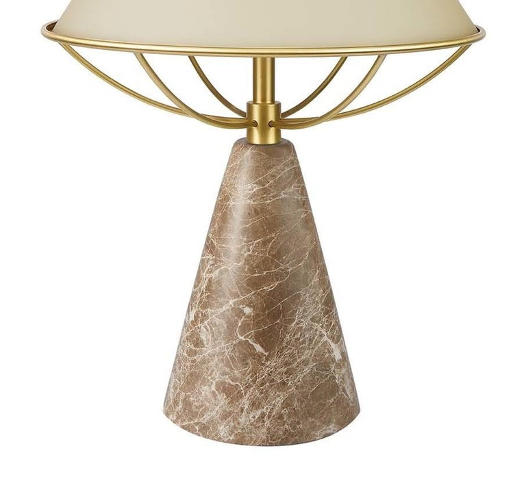 This stunning table lamp was designed by Lorenza Bozzoli and is part of the Anita collection. It features a stunning conical base in Emperador marble with a structure of satin-finished brass made up of curved elements that support the