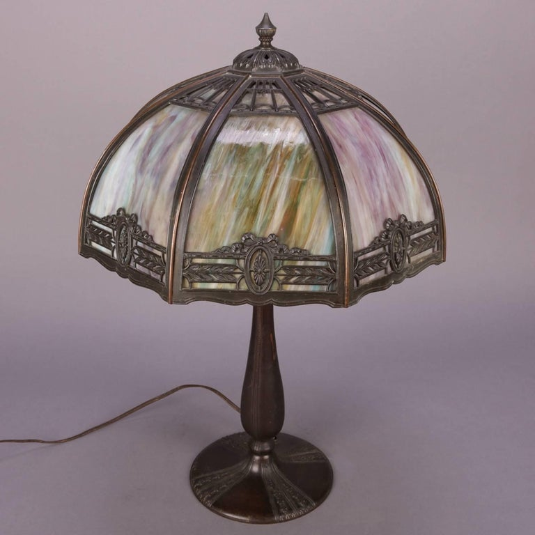 Antique Bradley & Hubbard School table lamp features eight panel pierced filigree shade with foliate border containing patera medallions central to each panel and housing curved slag glass panes, cast base is tulip form with dual pull chain light