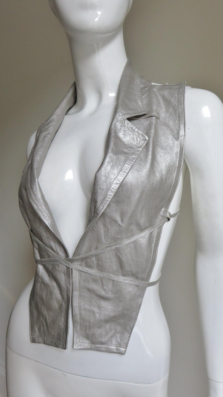 A fabulous silver grey leather vest from one of the Antwerp six, Ann Demeulemeester.  It has the appearance of a sleeveless jacket front with lapels.  The 2 front panels can be hooked closed of left open.  The adjustable matching silver straps cross