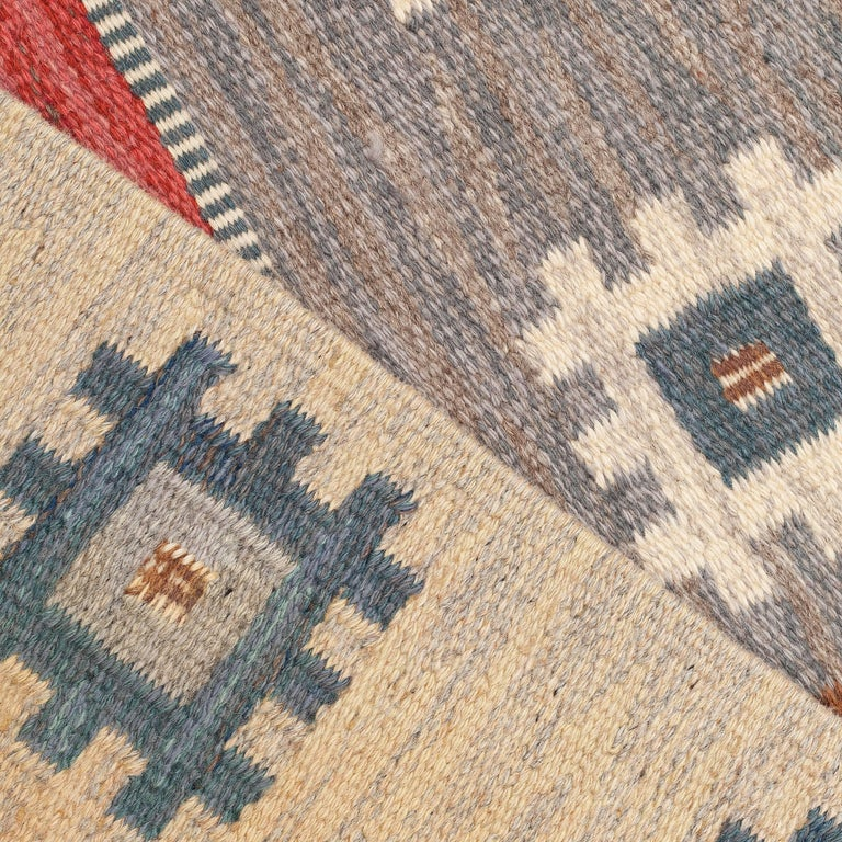 A handwoven modernist flat-weave carpet / rug by Anna-Greta Sjöqvist. Most likely woven in the 1950s. Tones include red, white, blue, beige and brown. Handwoven in pure wool, using a Kilim technique. Signed AGS for Anna-Greta Sjöqvist.