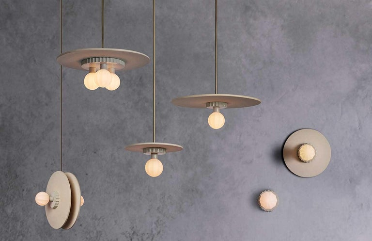 This family of lights are composed of hand blown ridged glass, a glazed scalloped puck and topped off with a large unglazed ceramic disc. The difference in texture between the elements are picked up beautifully by the light.