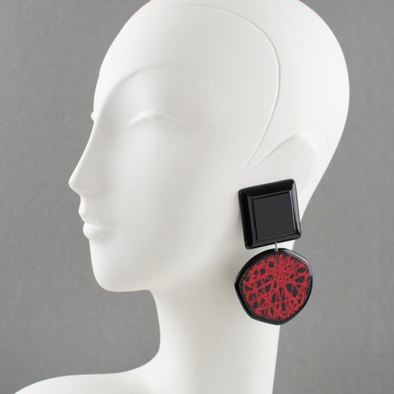 Charming Anne and Frank Vigneri Lucite clip-on earrings. Oversized geometric dangling design with square and free-form disc shape in licorice black Lucite or resin. The disc is ornate with a textured red design similar to intersecting lines. No