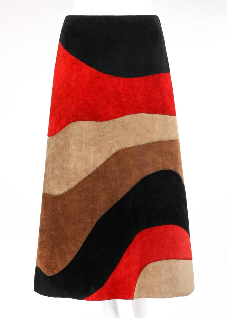 Vintage Anne Klein c.1970's red black brown color block suede leather a-line skirt. Designed by Donna Karan. Color blocked wave pattern suede leather in shades of black, red, beige, and brown. Zig-zag overlay stitch detail throughout. Raw edge hem.