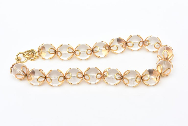 This great original vintage Anne Klein chunky lucite ball and gold filed embellished loop design necklace is from when Anne Klein was still living. The series of loops surround the top and bottom of each lucite ball. It is from the 80's and ever