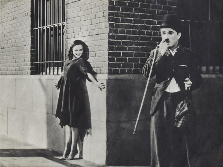 Charlie Chaplin is a vintage black and white photograph realized during the 1930s.  Includes a wood frame.   This pretty photograph represents the actor Charlie Chaplin with a woman, probably during one of his famous sketches.  Very good