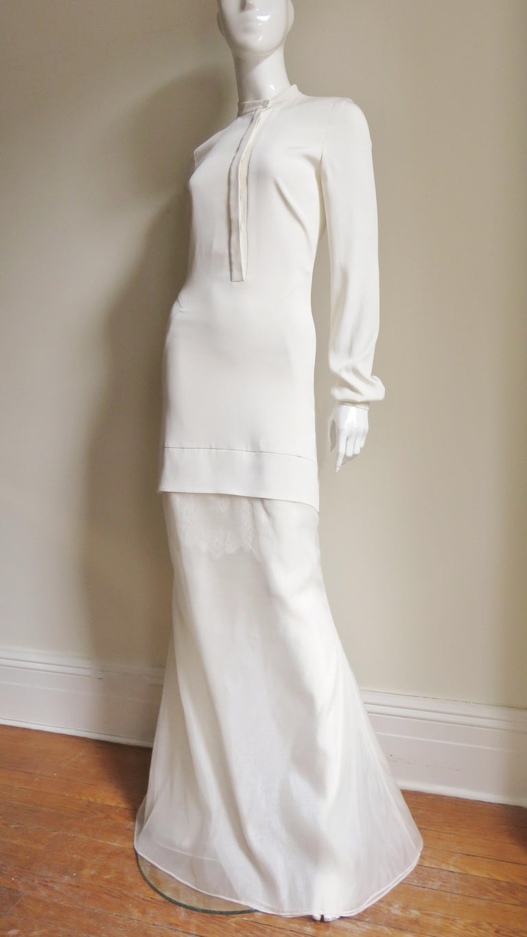A gorgeous, ethereal off white silk gown, maxi dress from Antonio Berardi.   It has a crew neckline and hidden button front placket.  The long sleeves have a circular mother of pearl button with a black center on each cuff.  The mid thigh length
