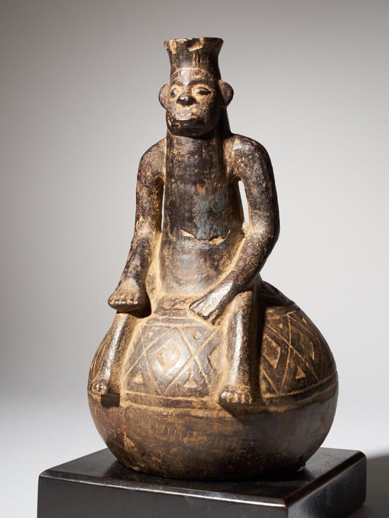 This fine, round, dark grey vessel depicts a complete figure which is rare. It was made by the Mangbetu People. The Mangbetu ethnic group lives deep in the center of Africa. They were famous for their hair styles and practiced Lipombo, the art of