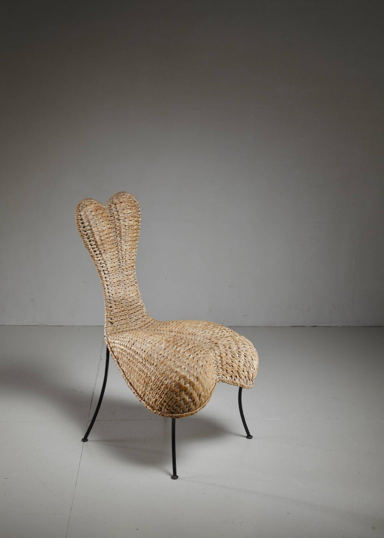 An anthropomorphic chair made of woven cane, standing on metal legs. Beautiful organic shaped object chair.