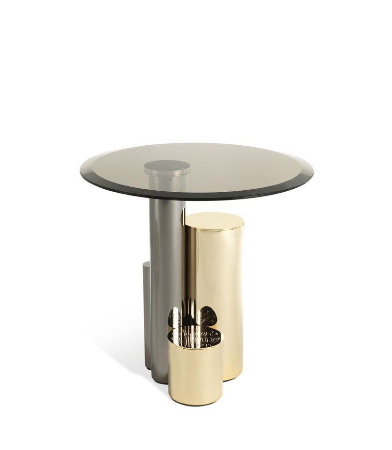 Contemporary lines and precious materials for Antigua side table. The base is created by a combination of different materials and colors: a sculptural composition consisting of metal elements with different thicknesses, heights and finishes that