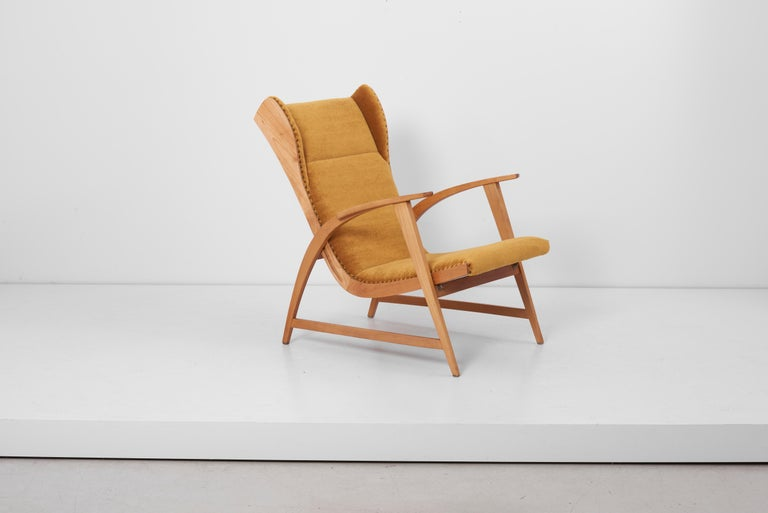 Lounge chair from the Knoll Antimott series. Manufactured in the 1950s by Wilhelm Knoll in Germany. Wooden base and professionally newly reupholstered in a high end amber mohair fabric by Kvadrat. A matching rocking chair is also listed