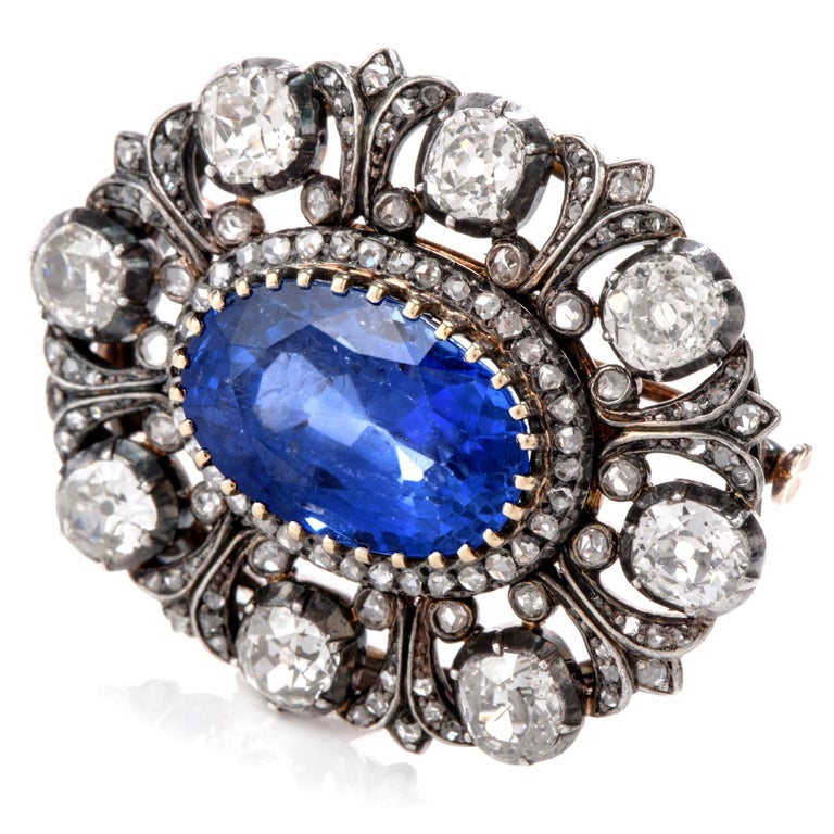 This Rare antique English Edwardian era Diamond and sapphire  brooch was inspired in a Halo and Flor De Lis motif and crafted in 18K gold with top silver.  Adorning the center is a No Heat oval Ceylan sapphires measuring appx. 15.53mm x 10.70mm and