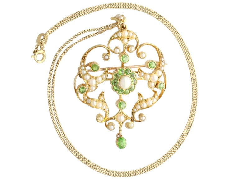 A stunning, fine and impressive antique 1.19 carat demantoid garnet and seed pearl, 15 karat yellow gold pendant / brooch; part of our diverse gemstone jewelry and estate jewelry collections  This stunning, fine and impressive antique pendant has