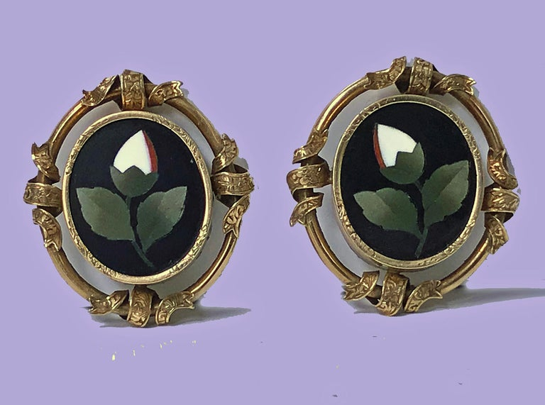 Pair of Antique 14K Pietra Dura Earrings, C.1875. Each of oval form, bezel set oval pietra dura floral white, green orange inlay colours, the surround gold mount interspaced ribbon design, clip fitments. Gold acid tests 14K. Measures: 1.25 x 1.00
