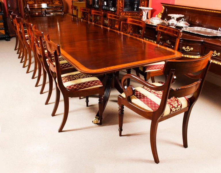 This is a superb antique 14ft Regency Revival dining table, crafted in flame mahogany and featuring superb satinwood crossbanded decoration, and dating from the late 19th century.  Capable of seating fourteen people in Regal comfort it is an