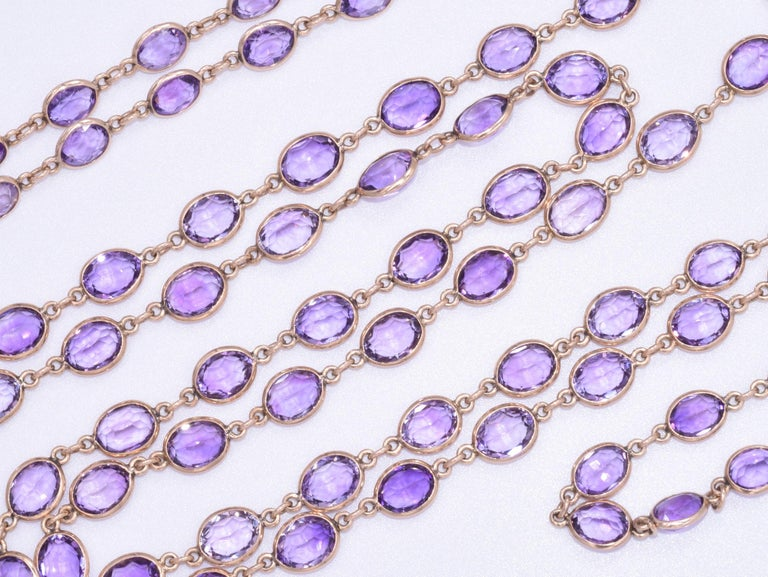 This antique yellow gold oval amethyst chain features, ninety-nine oval amethysts totaling approximately 100 carats are mounted in 14 karat yellow gold eyeglass bezels measuring 60 inches in length. Antique cut oval amethysts measure an average of