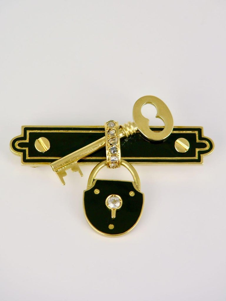 A 15k yellow gold black enamel diamond lock and key brooch - a late 19th century pin of a unique design of a padlock decorated in black enamel with an old cut diamond set within the key hole and suspended below a black enamel bar brooch with screw