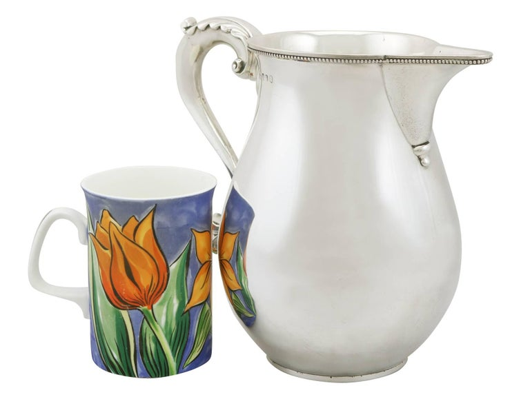 A magnificent, fine and impressive antique George III English sterling silver beer or water jug by Thomas Chawner; part of our dining silverware collection.  This magnificent antique George III sterling silver beer jug has a plain baluster form