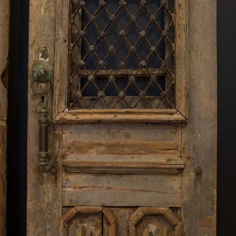 About  This a pair of original wooden castle doors with steel grate and substantial bronze hardware. The doors feature intricately carved heads of the man and woman of the house positioned at the top of each door. Shutters are on the backside that