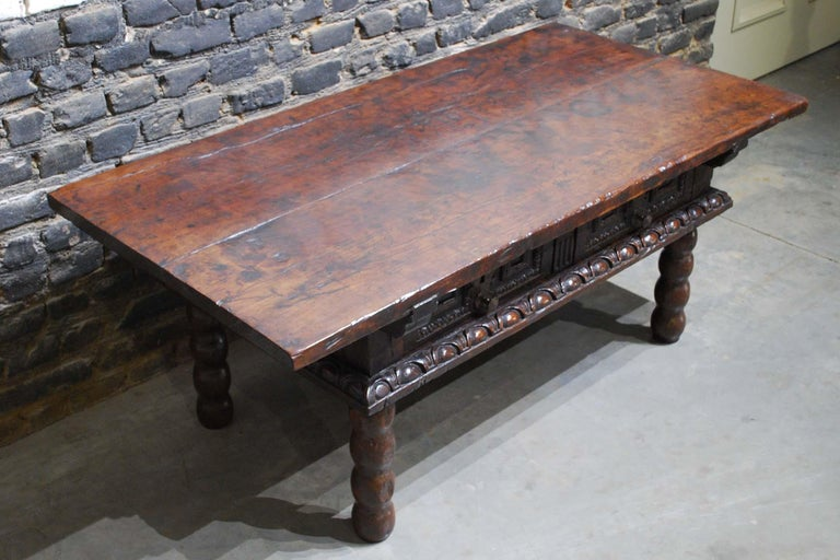 A rustic walnut coffee table that originates in Spain circa 1680. Its top is made from two pieces of solid thick walnut with beautiful grain. Below two drawers are situated. The drawer fronts have a hand carved gadrooned mold and elevated panels.