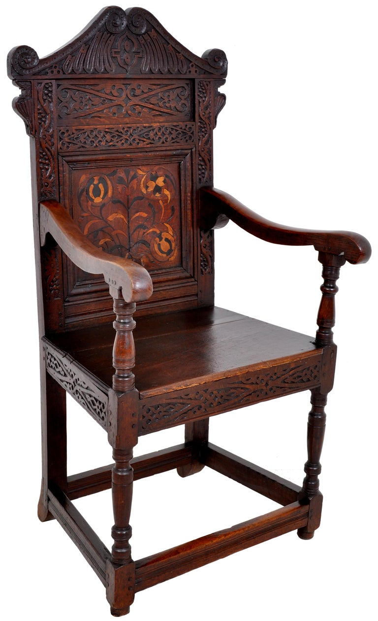 A rare antique inlaid oak carved Wainscot chair, Charles II period, circa 1670. The chair having a carved top rail pediment, the back carved with fruiting vines and geometric devices. To the center of the chair back is an inlaid floral panel of