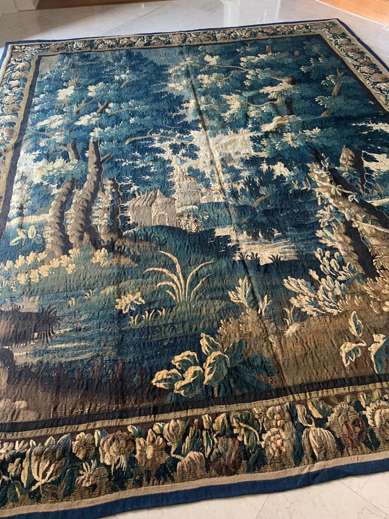 This is a gorgeous antique square 17th century flemish Verdure landscape tapestry without figures in a beautiful and rich summer scene of a countryside with lush trees and vegetation and homes in the distance. The border features several different