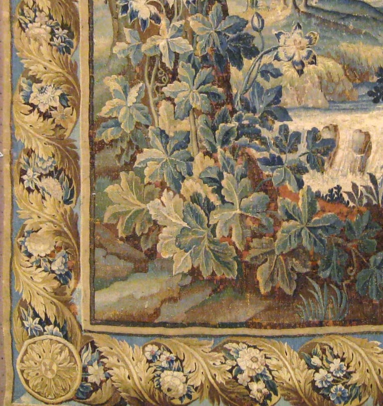 An antique 17th century Flemish verdure landscape tapestry, vertically oriented, size 9'4 H x 5'7 W. This handwoven tapestry depicts a pair of exotic birds in a tranquil verdant landscape, with one standing by a stream in the greenery at bottom