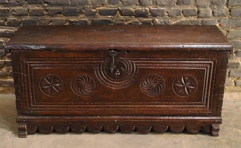 A beautiful trunk or coffer from Northern Spain that was made in the first part of the 17th century. It features a rectangular hinged molded top over a deeply carved base. The front of the chest has five geometric circular carvings surrounded by a