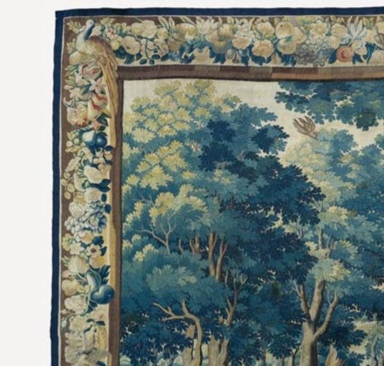This is a gorgeous antique 17th century Flemish verdure landscape tapestry depicting a beautiful and rich summer scene of a countryside with lush trees and vegetation, with two figures in the foreground. The border features several different