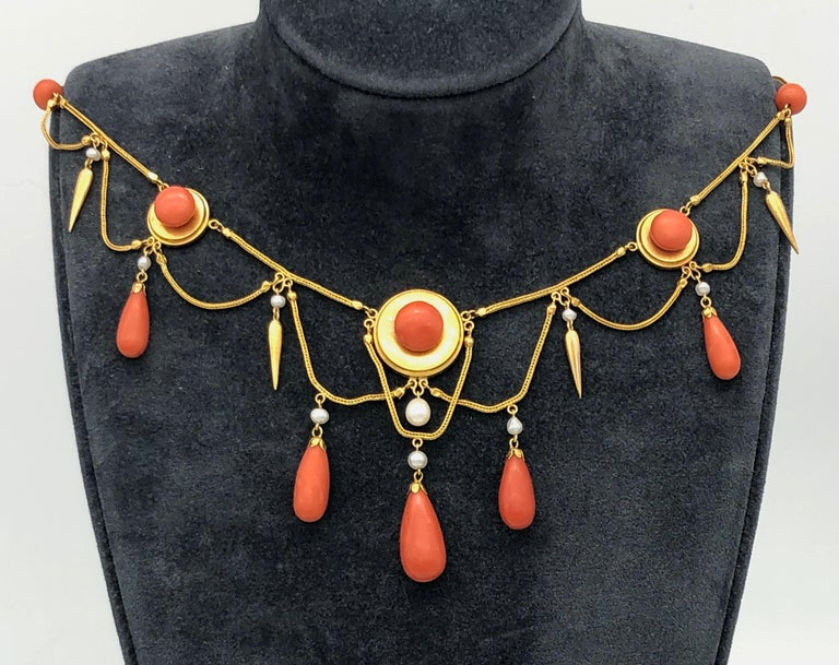 Very elegant and delicate necklace made out of 18 karat gold around 1870 in the neo archeological style. Fine fox tail chains alternate with coral beads and round gold disks reminiscent of targets. The disks, the larger one as centrepiece of the
