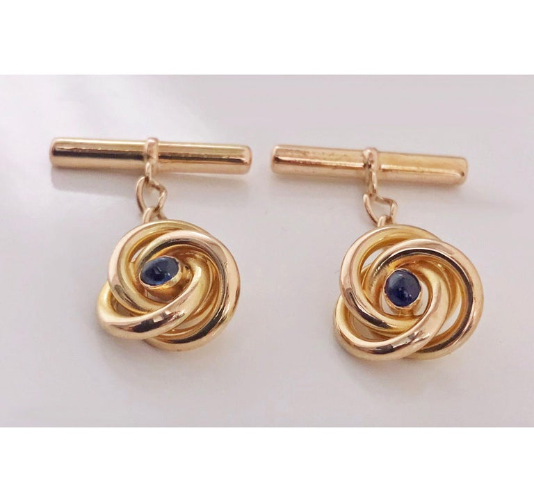 Pair of 18-karat (tested) sapphire cufflinks, circa 1930. Each of open swirl knot design, set with small oval cabochon blue sapphire, 14-karat bar fitments chain link between. Total item weight: 4.59 gm. Continental mark, possibly French.