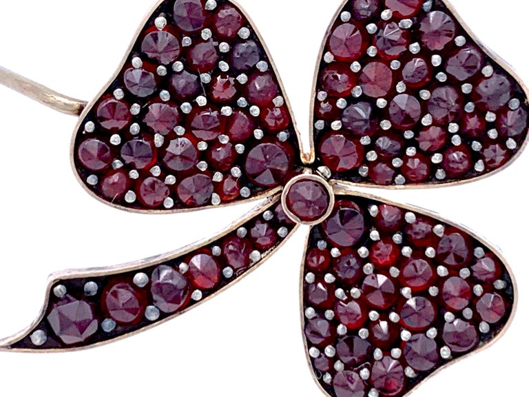 This brooch in the shape of a three leaf clover is set with bohemian garnets and was a gift for good luck. The garments are set in 9 karat gold.