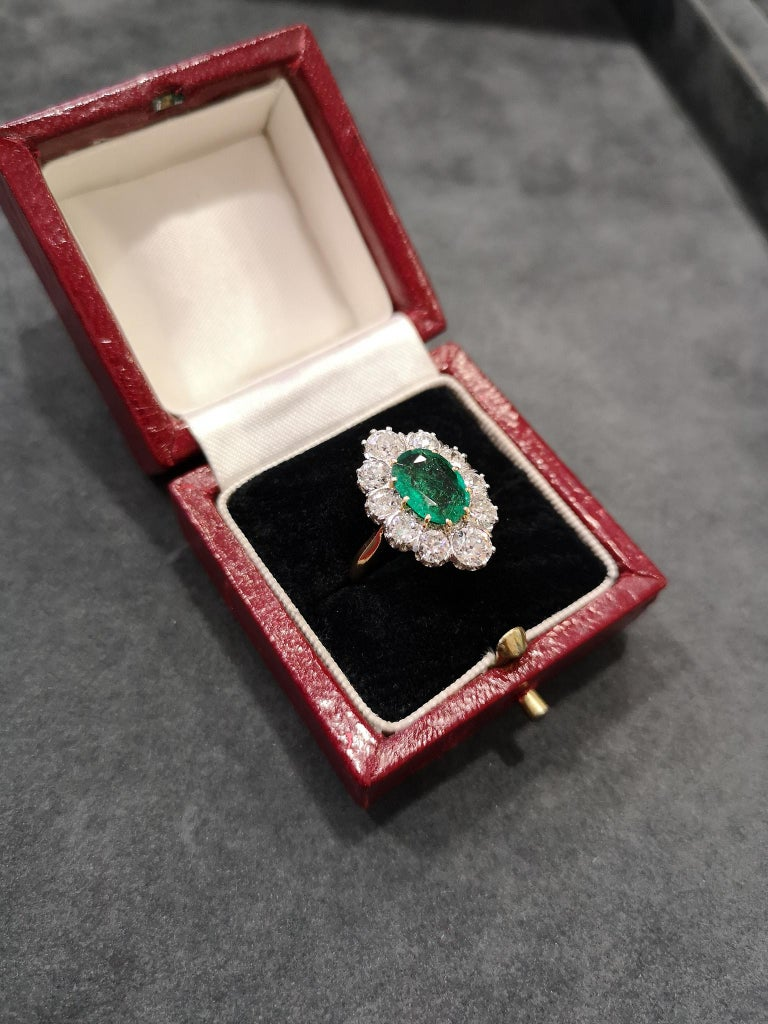 A beautiful quality antique navette cluster ring. The large, deep green oval-cut emerald, surrounded generously with 10 old-cut diamonds, mounted in platinum. A polished, 18-carat gold shank, with French assay marks. Circa 1915. Tests as 18 carat