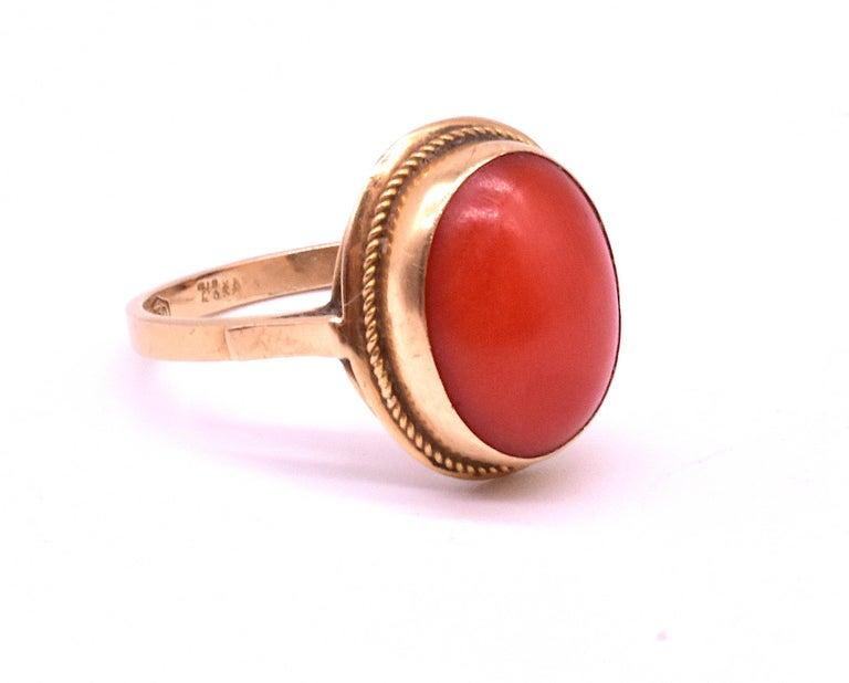 An Antique Yellow gold ring with a 5/8 inch diameter round, beautifully colored smooth cabochon coral at the center and millegrain detail in the gold border.  A classic, simple pretty Victorian coral ring from the 1880's. The ring is a size 7.