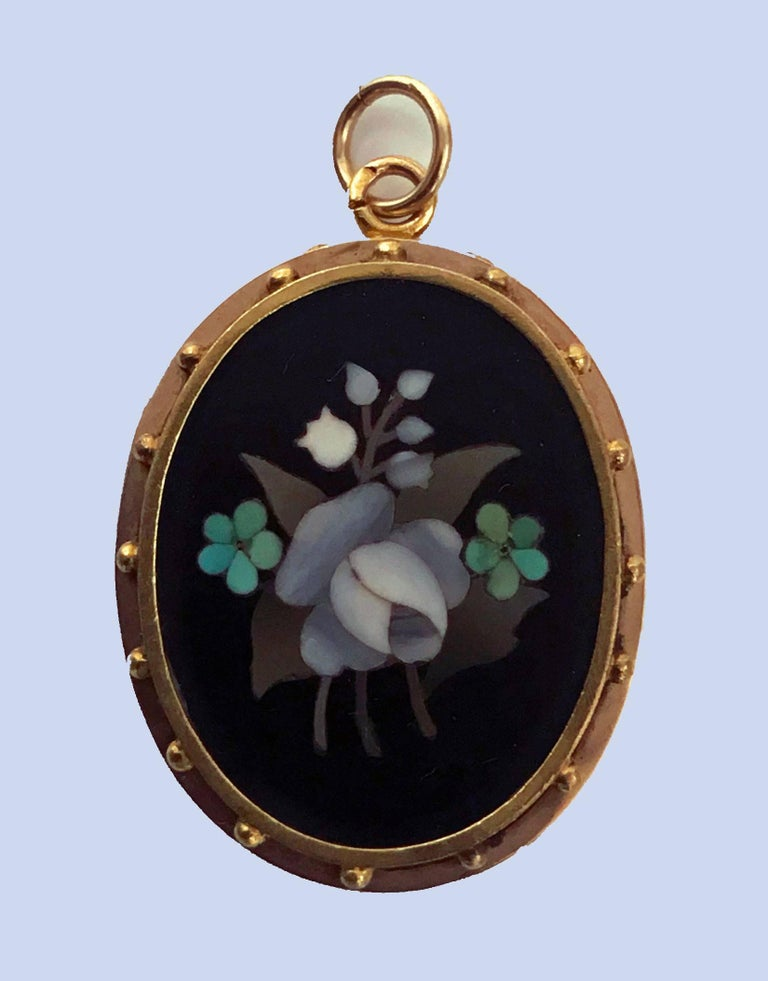 Antique 18K Gold Pietra Dura Pendant Locket, Italy C.1875. The Pendant Locket of oval shape, fine pietra dura floral white, green, lilac inlay colors, the surround gold mount of bead work. The reverse with hinged vacant locket. Gold acid tests 18K.
