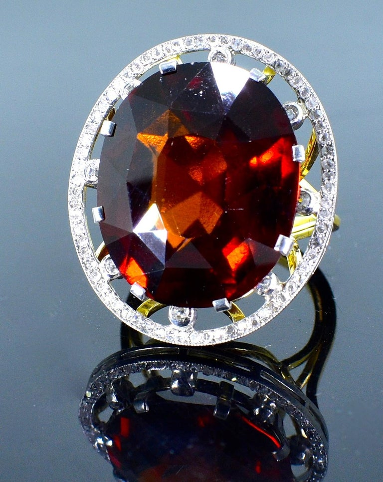 Antique ring centering a fine and unusual orange garnet weighing 26 cts., and displaying a fine deep orange/red color.  Surrounding this antique cushion cut stone are rose cut and European cut diamonds.  This ring is in fine condition and a size