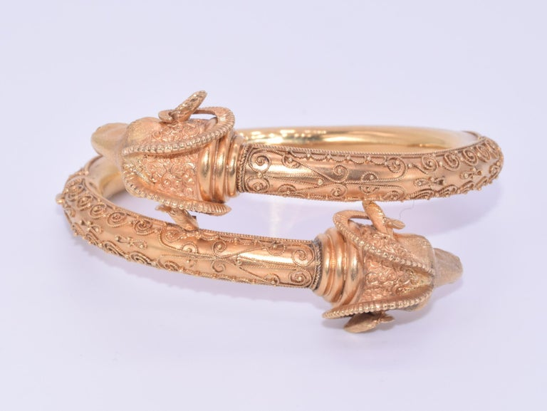 A hinged bypass bangle formed in 18 karat yellow gold features a pair of highly detailed ram's heads with granulation and scrolling wirework accents. Inner circumference approximately 6.5 inches. Each ram's head measures approximately 1 inch wide.