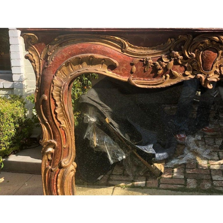Antique 18th century Venetian style red giltwood over mantel mirror. Once a fireplace surround, converted to a mirror.