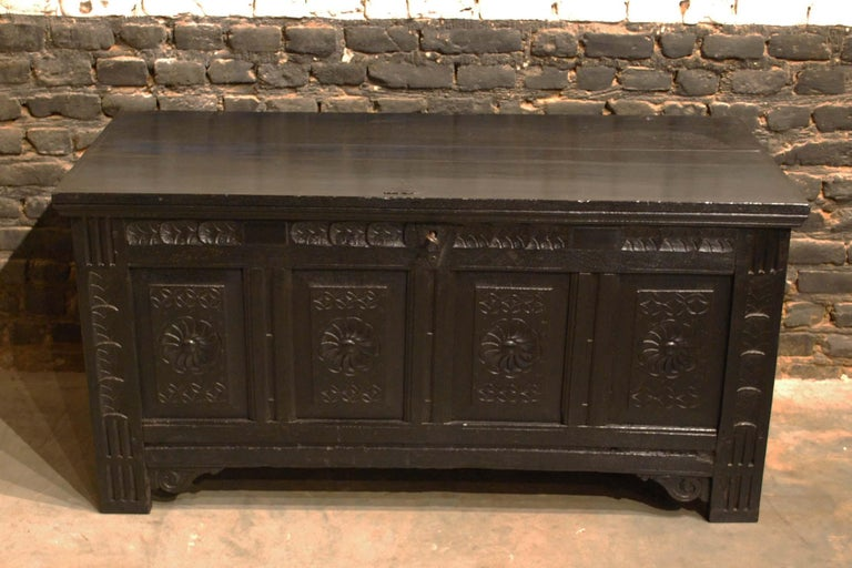 This beautiful black colored Renaissance chest or coffer was made in the early 18th century. It was made in the finest quality summer oak and stained very dark, almost black. The front of the piece has four panels with handsome carved circular