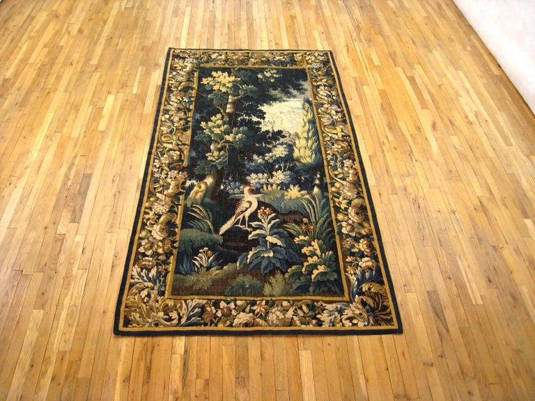 An antique 18th century Flemish verdure landscape tapestry, size: 8.0 H x 4.6 W. This fine handwoven European wall hanging features a lovely landscape scene, with an exotic bird in a lush verdant setting. Enclosed within an elaborate scrolling