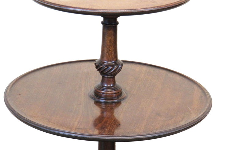 A very good quality 18th century Georgian mahogany dumbwaiter retaining excellent untouched colour and patina with three graduated revolving circular dished tiers united by turned central column with crisply carved decoration raised on elegant
