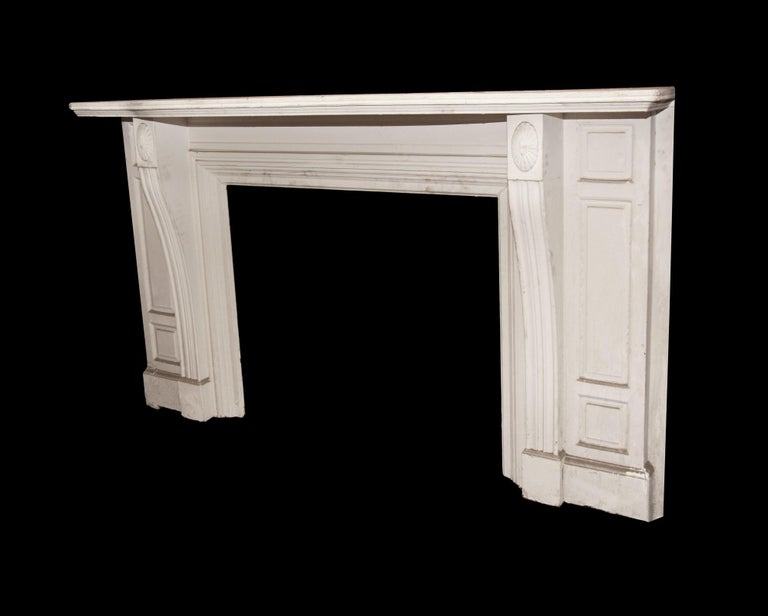 This is an antique wooden mantel from the early 1900s. Simple yet elegant design with fluted pilasters on each side along with top rondels. Oversized shelf has an convex curve. Overall condition is good.