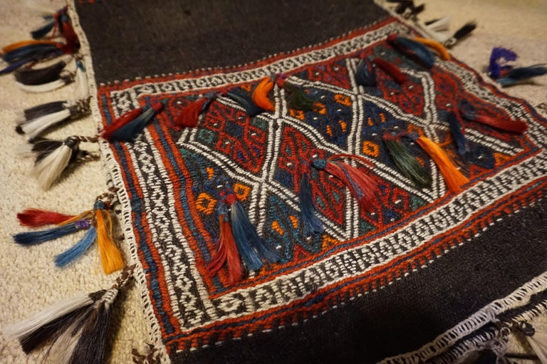 Fine example of older Turkish saddle bag with 1926 export seal. Lovely colorful kite shape pattern juxtaposed against a dark brown near black background. In good condition,  circa 1920s.