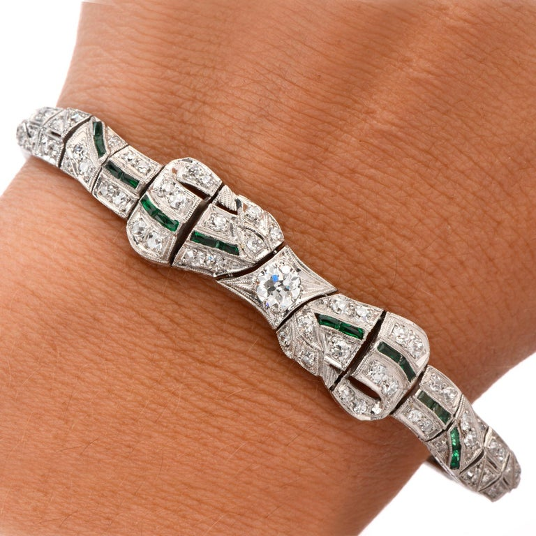 This Antique 1930's Ribbon and Bow inspired Diamond and Emerald Bracelet was crafted in luxurous Platinum.  The bracelet drips in Diamonds from one end of the Ribbon to the other featuring an Emerald thread through the center.  This can be both the